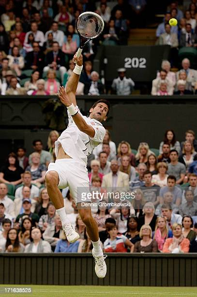 Novak Djokovic of Serbia leaps to smash the ball during his Gentlemen's Singles second round match against Bobby Reynolds of the United States of...