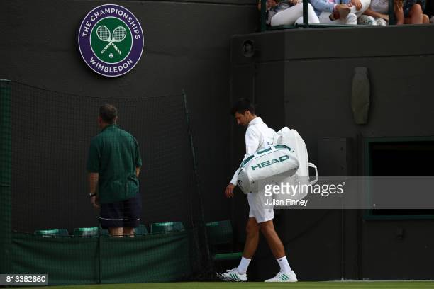 Novak Djokovic of Serbia leaves court as he retires injured during the Gentlemen's Singles quarter final match against Tomas Berdych of The Czech...