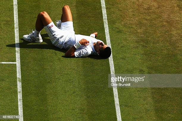 Novak Djokovic of Serbia lies on the grass after slipping over during his Gentlemen's Singles quarterfinal match against Marin Cilic of Croatia on...