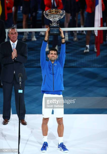 Novak Djokovic of Serbia lifts the Norman Brookes Challenge Cup following victory in his Men's Singles Final match against Rafael Nadal of Spain...