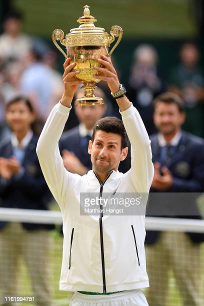 Novak Djokovic of Serbia lifts the trophy after winning his Men's Singles final against Roger Federer of Switzerland during Day thirteen of The...