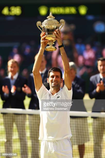 Novak Djokovic of Serbia lifts the trophy after winning the Men's Singles final against Kevin Anderson of South Africa on day thirteen of the...
