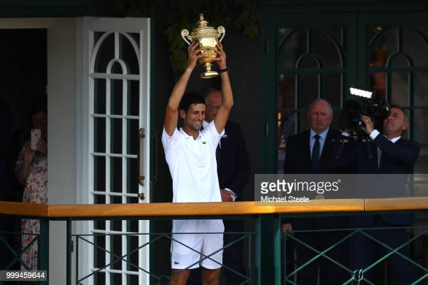 Novak Djokovic of Serbia lifts the trophy on the balcony of Centre Court after winning the Men's Singles final against Kevin Anderson of South Africa...