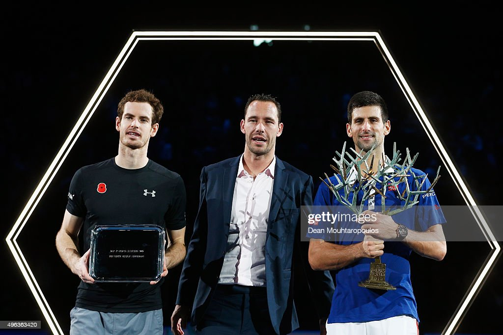 Novak Djokovic (R) of Serbia lifts the winners trophy after victory against Andy Murray (L) of Great Britain after their Mens Final match as they pose with Michael Llodra (C) during Day 7 of the BNP Paribas Masters held at AccorHotels Arena on November 8, 2015 in Paris, France.