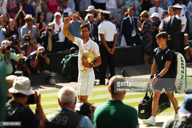 Novak Djokovic of Serbia looks back towards his players' box as he celebrates with the trophy after winning the Men's Singles final against Kevin...