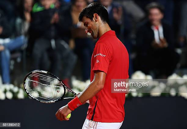 Novak Djokovic of Serbia looks on after breaking a string on his racquet during his match against Kei Nishikori of Japan during day seven of The...