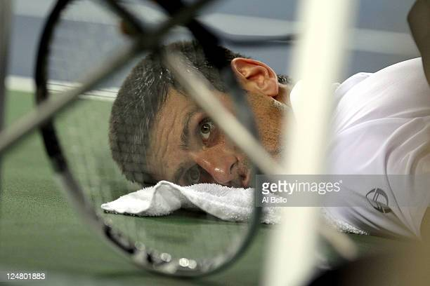 Novak Djokovic of Serbia looks on as he receives treatment on his back from ATP Trainer Clay Sniteman against Rafael Nadal of Spain during the Men's...