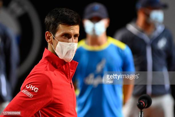 Novak Djokovic of Serbia looks on wearing a mask in the presentation ceremony after winning his men's final match against Diego Schwartzman of...