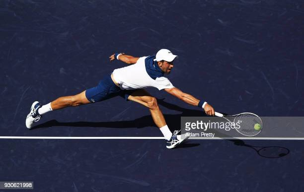 Novak Djokovic of Serbia lunges for a backhand during his match against Taro Daniel of Japan during the BNP Paribas Open at the Indian Wells Tennis...