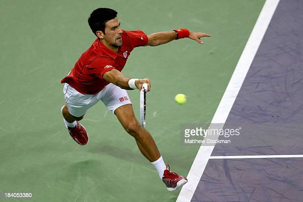 Novak Djokovic of Serbia lunges for a ball while playing Gael Monfils of France during the Shanghai Rolex Masters at the Qi Zhong Tennis Center on...