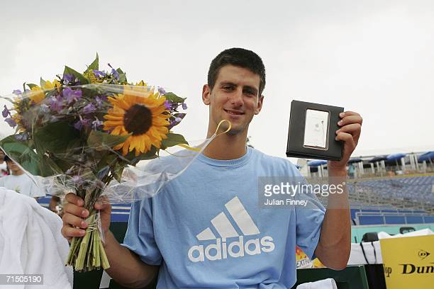 Novak Djokovic of Serbia Montenegro celebrates defeating Nicolas Massu of Chile in straight sets with his prize an ipod and some flowers after the...