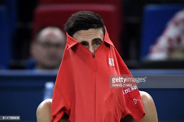 Novak Djokovic of Serbia peeks out of his shirt during his men's singles semifinals match against Roberto Bautista Agut of Spain at the Shanghai...