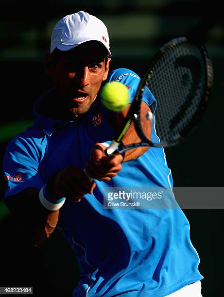 Novak Djokovic of Serbia plays a backhand against Alexandr Dolgopolov of the Ukraine in their fourth round match during the Miami Open Presented by...