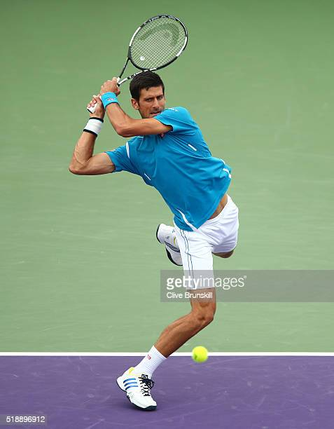 Novak Djokovic of Serbia plays a backhand against Kei Nishikori of Japan in the mens final during the Miami Open Presented by Itau at Crandon Park...