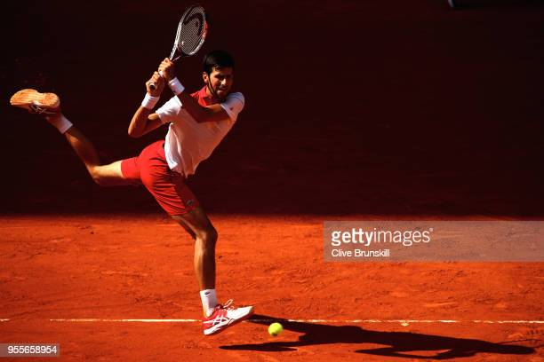 Novak Djokovic of Serbia plays a backhand against Kei Nishikori of Japan in their first round match during day three of the Mutua Madrid Open tennis...