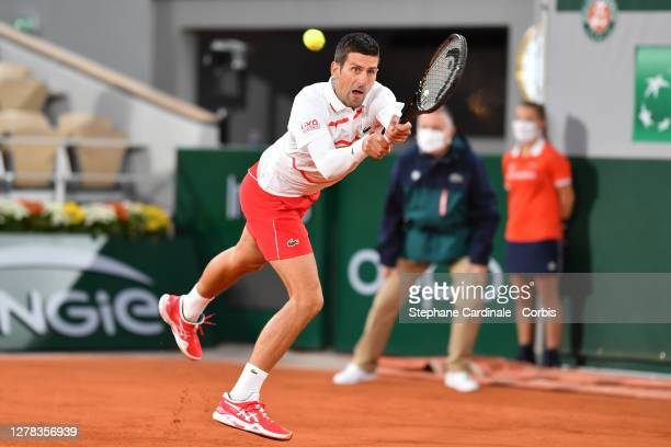 Novak Djokovic of Serbia plays a backhand during his Men's Singles third round match against Daniel Elahi Galan of Colombia on day seven of the 2020...