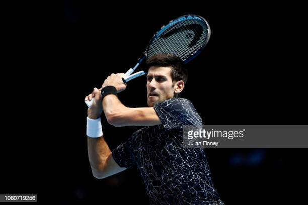 Novak Djokovic of Serbia plays a backhand during his round robin match against John Isner of The United States during Day Two of the Nitto ATP Finals...