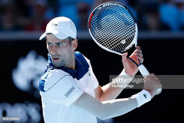 Novak Djokovic of Serbia plays a backhand in his first round match against Donald Young of the United States on day two of the 2018 Australian Open...
