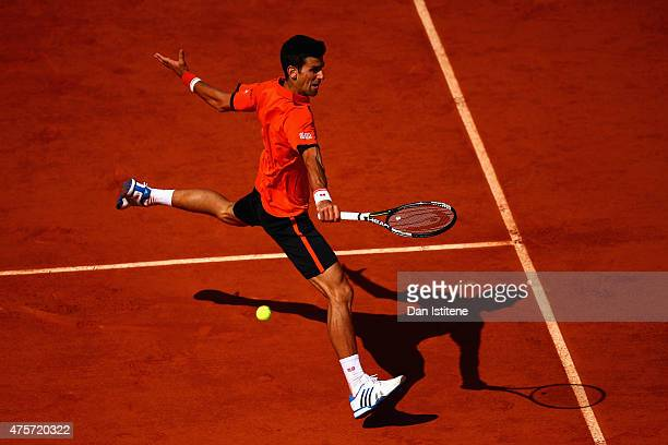 Novak Djokovic of Serbia plays a backhand in his Men's quarter final match against Rafael Nadal of Spain on day eleven of the 2015 French Open at...