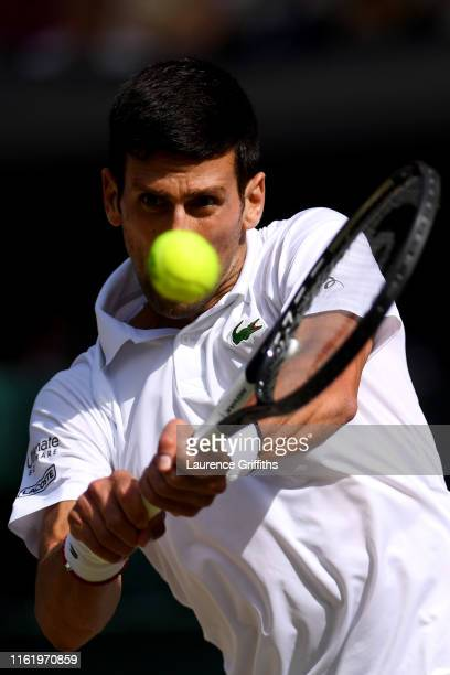 Novak Djokovic of Serbia plays a backhand in his Men's Singles final against Roger Federer of Switzerland during Day thirteen of The Championships -...