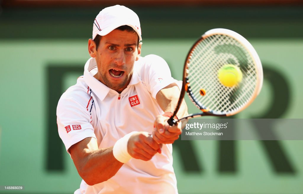 Novak Djokovic of Serbia plays a backhand in his men's singles first round match against Potito Starace of Italy during day 2 of the French Open at Roland Garros on May 28, 2012 in Paris, France.