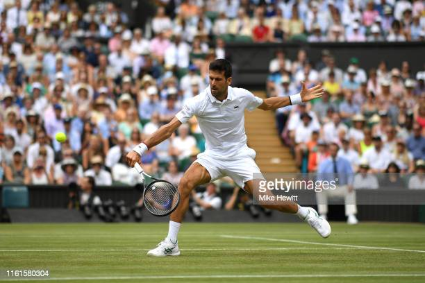 Novak Djokovic of Serbia plays a backhand in his Men's Singles semifinal match against Roberto Bautista Agut of Spain during Day eleven of The...
