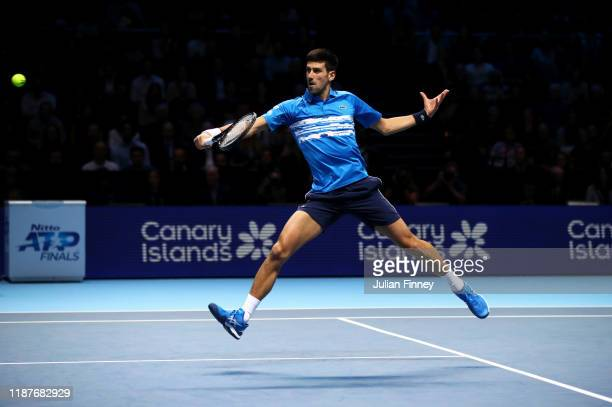 Novak Djokovic of Serbia plays a backhand in his singles match against Roger Federer of Switzerland during Day Five of the Nitto ATP World Tour...
