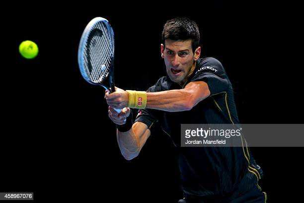 Novak Djokovic of Serbia plays a backhand in the round robin singles match against Tomas Berdych of Czech Republic on day six of the Barclays ATP...