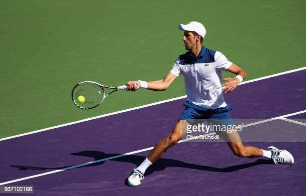 Novak Djokovic of Serbia plays a forehand volley against Benoit Paire of France in their second round match during the Miami Open Presented by Itau...