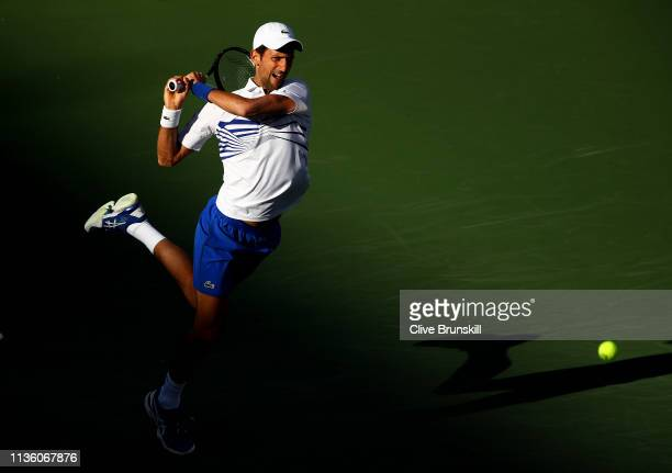 Novak Djokovic of Serbia plays a forehand while playing with Fabio Fognini of Italy against Lukasz Kubot of Poland and Marcelo Melo of Brazil during...