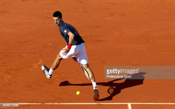 Novak Djokovic of Serbia plays a trick shot between his legs to return the ball during his men's singles semi final match against Roger Federer of...
