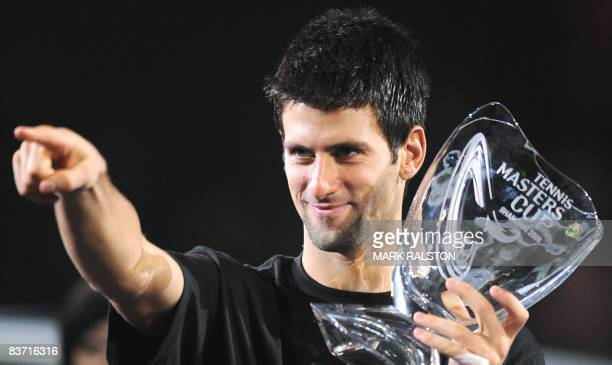 Novak Djokovic of Serbia points to his girlfriend in the stands as he holds the winner's trophy following his victory over Nikolay Davydenko of...