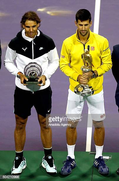 Novak Djokovic of Serbia poses for a photo with his winning trophy next to Rafael Nadal of Spain holding his second place trophy after the Qatar...