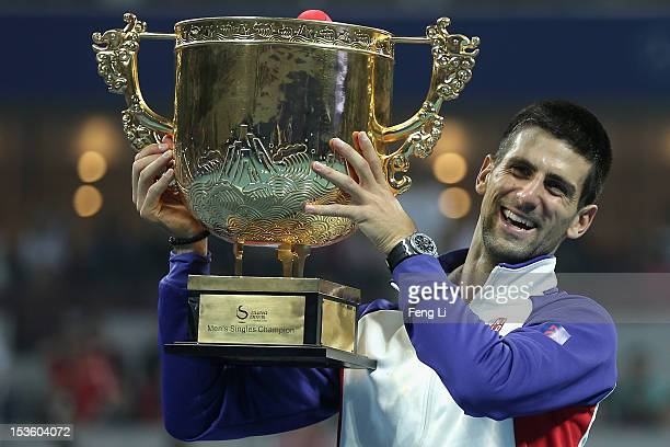 Novak Djokovic of Serbia poses for photographers after defeqating Jo-Wilfried Tsonga of France during the Men's Single Final of the China Open at the...