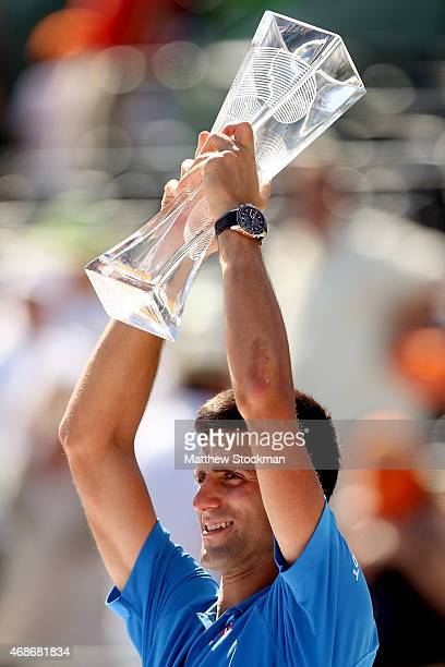 Novak Djokovic of Serbia poses for photographers with the Butch Buchholz Trophy after defeating Andy Murray of Great Britain during the final on day...