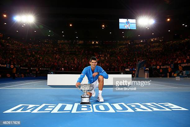 Novak Djokovic of Serbia poses for photographers with the Norman Brookes Challenge Cup after winning his men's final match against Andy Murray of...
