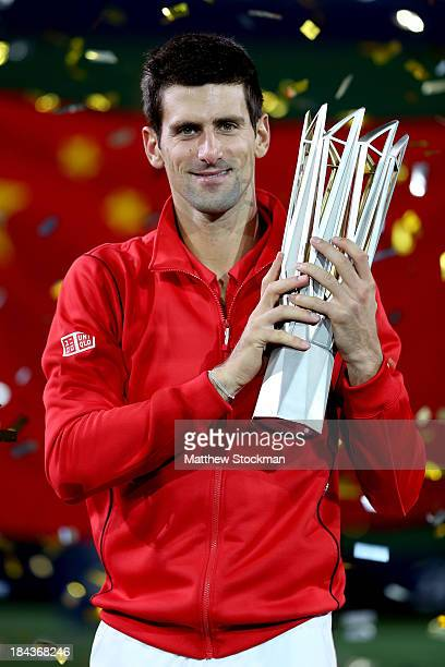 Novak Djokovic of Serbia poses for photographers with the winner's trophy after defeating Juan Martin Del Potro of Argentina during the final of the...