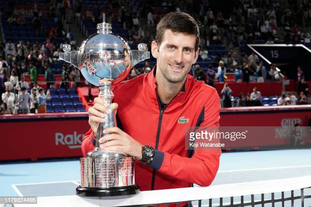 Novak Djokovic of Serbia poses for photographs with the trophy after the Singles final against John Millman of Australia on day seven of the Rakuten...