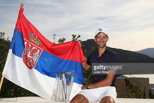 Novak Djokovic of Serbia poses with his flag and trophy after his win over Milos Raonic of Canada during day fourteen of the BNP Paribas Open at...