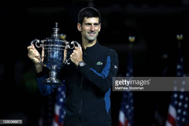 Novak Djokovic of Serbia poses with the championship trophy after winning his men's Singles finals match against Juan Martin del Potro of Argentina...