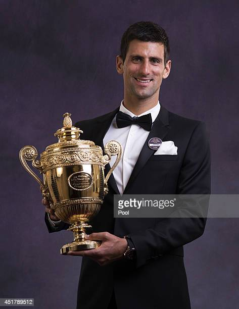 Novak Djokovic of Serbia poses with the Gentlemen's Singles Trophy at the Wimbledon Championships 2014 Winners Ball at The Royal Opera House on July...