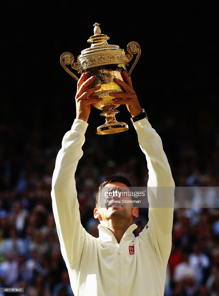 Novak Djokovic of Serbia poses with the Gentlemen's Singles Trophy following his victory in the Gentlemen's Singles Final match against Roger Federer of Switzerland on day thirteen of the Wimbledon Lawn Tennis Championships at the All England Lawn Tennis and Croquet Club on July 6, 2014 in London, England.