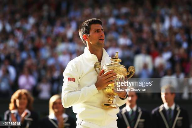 Novak Djokovic of Serbia poses with the Gentlemen's Singles Trophy following his victory in the Gentlemen's Singles Final match against Roger Federer...