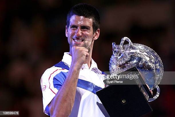 Novak Djokovic of Serbia poses with the Norman Brookes Challenge Cup after winning his men's final match against Andy Murray of Great Britain during...