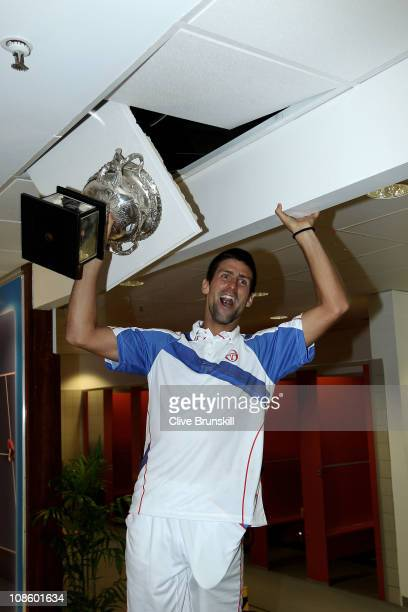 Novak Djokovic of Serbia poses with the Norman Brookes Challenge Cup in the players locker room after winning the men's final match against Andy...