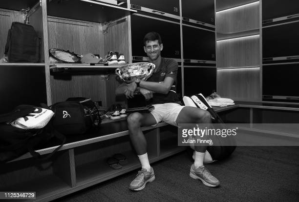 Novak Djokovic of Serbia poses with the Norman Brookes Challenge Cup in the locker room following victory in his Men's Singles Final match against...