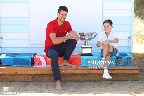Novak Djokovic of Serbia poses with the Norman Brookes Challenge Cup as he greets a young tennis fan after winning the 2021 Australian Open Men's...