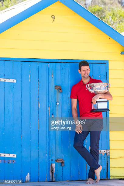 Novak Djokovic of Serbia poses with the Norman Brookes Challenge Cup in front of bathing box number 9 signifying the 9th Australian Open Men's title...