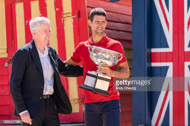 Novak Djokovic of Serbia poses with the Norman Brookes Challenge Cup beside Craig Tiley, CEO of Tennis Australia and tournament director of...