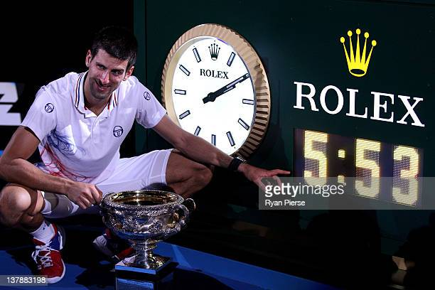 Novak Djokovic of Serbia poses with the Norman Brookes Challenge Cup and the clock after winning championship point and playing in the longest grand...